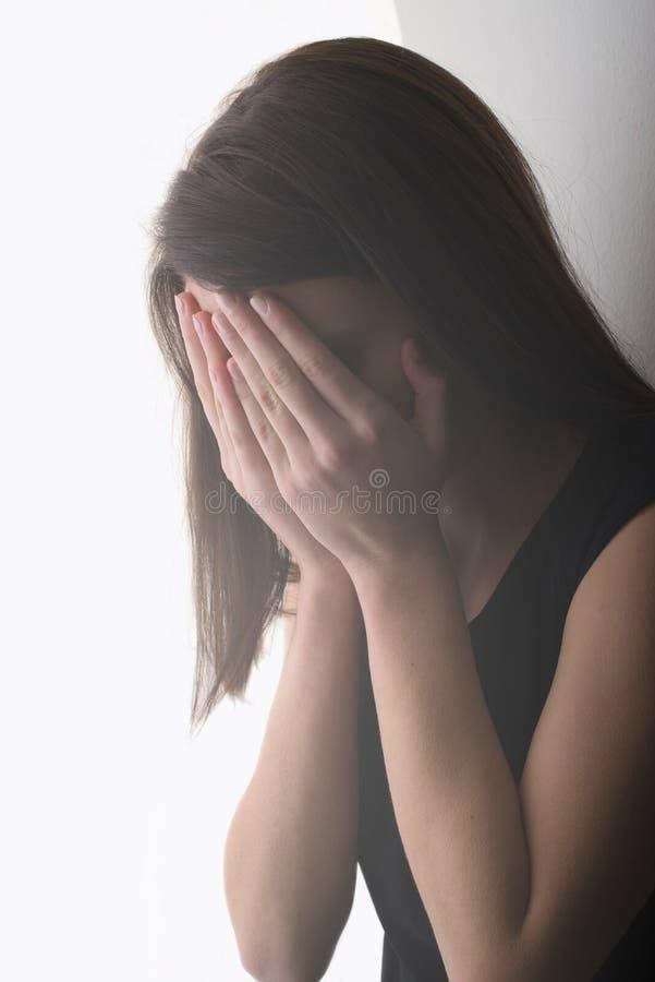哭泣和盖她的面孔的孤独的哀伤的女孩,当常设倾斜时 库存照片