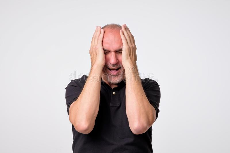 哭泣在他的手上的绝望成熟西班牙人 免版税库存照片
