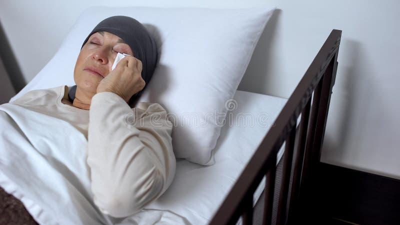 哭泣在医院病床上的女性患者,擦泪花与手帕,癌症 免版税库存照片