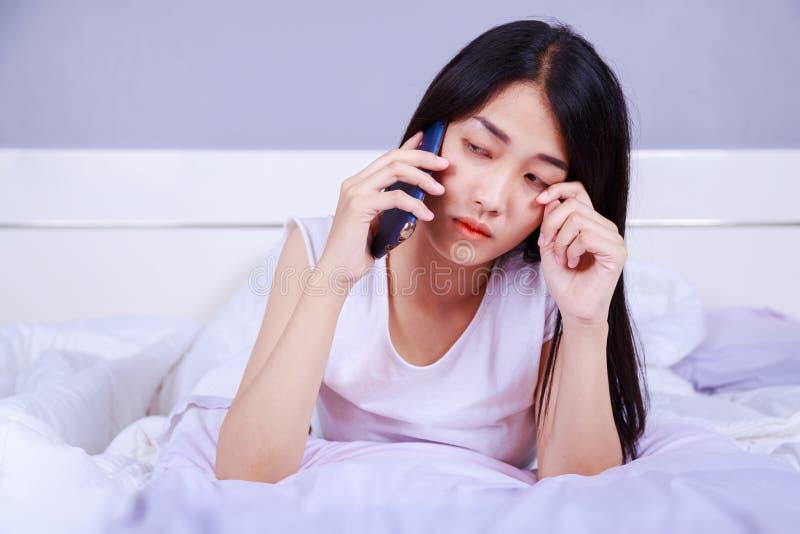 哭泣在她的床上的手机的妇女在卧室 免版税库存图片