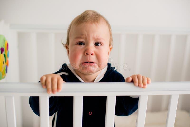 哭泣在小儿床的婴孩 免版税库存图片