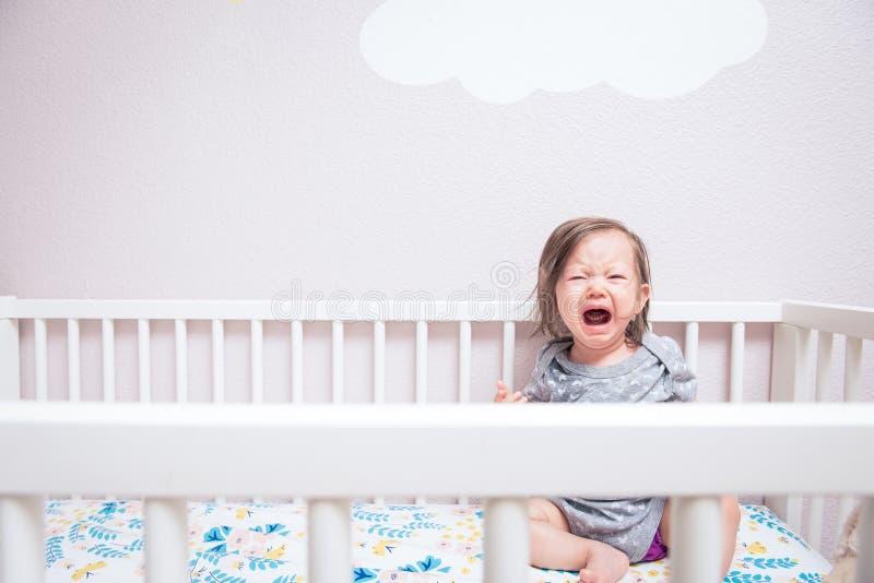 哭泣在小儿床的婴孩 免版税图库摄影