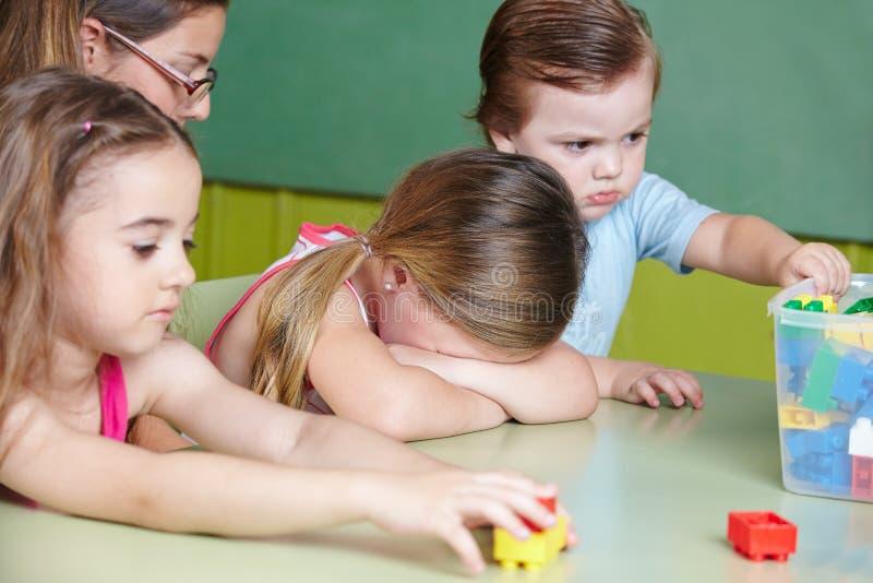 哭泣在幼儿园的哀伤的孩子 免版税库存图片