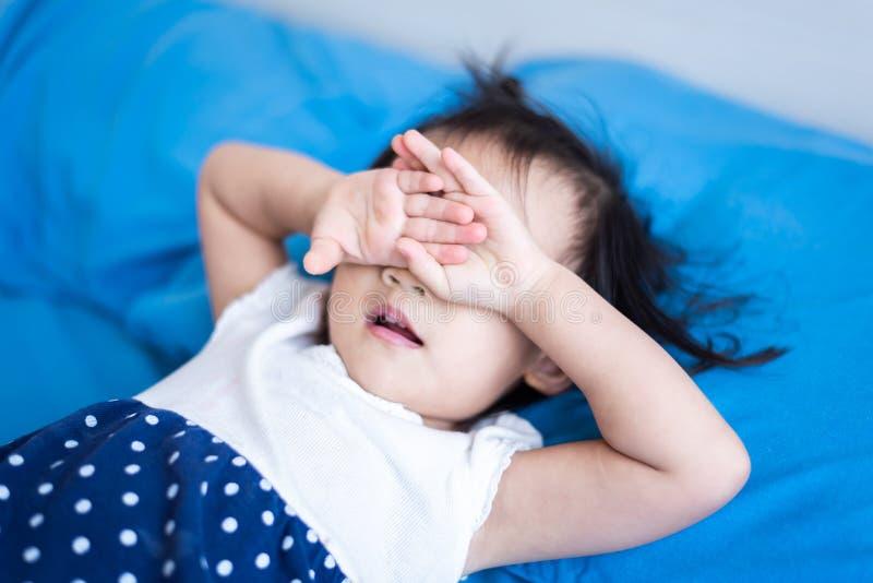 哭泣在床上的小孩子想念她的父亲 图库摄影