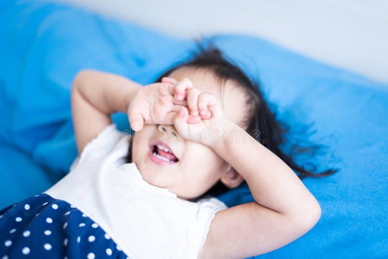 哭泣在床上的小孩子想念她的父亲 库存照片