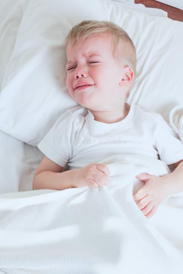 哭泣在床上的病的小孩男孩 免版税库存图片