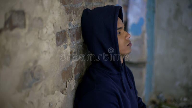 哭泣在房子里的绝望的十几岁的男孩毁坏被战争,消沉,贫穷 库存图片