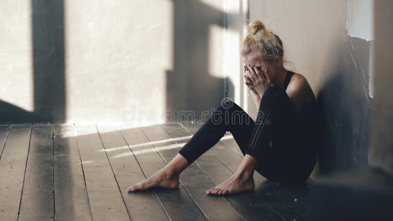 哭泣在损失perfomance以后的年轻十几岁的女孩舞蹈家特写镜头坐地板在大厅里户内 免版税库存照片