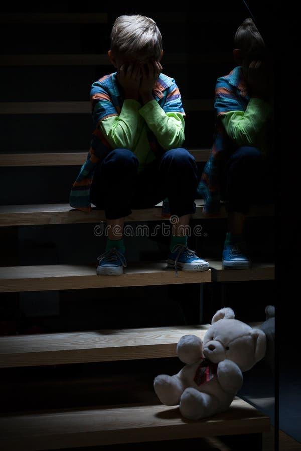 哭泣在晚上的男孩 免版税库存照片
