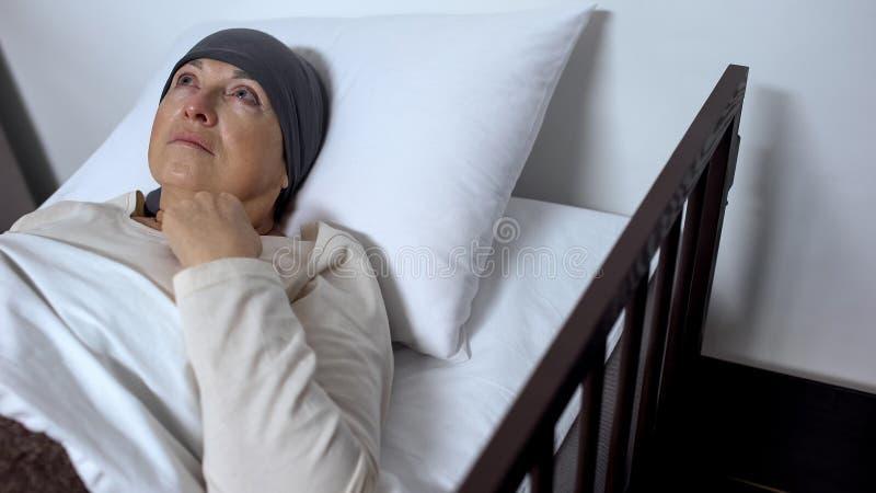 哭泣在病床的女性癌症患者,感到绝望和无能为力,祈祷 免版税库存照片