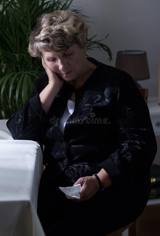 哭泣在葬礼以后的孤独的寡妇 免版税库存图片