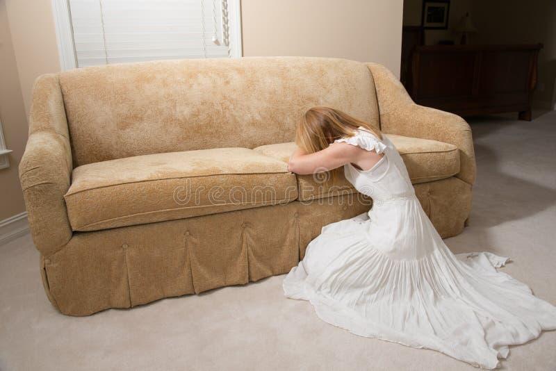 哭泣在长沙发的哀伤的妇女 库存图片