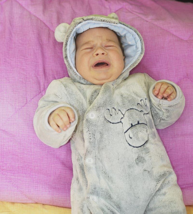 哭泣在他的床上的新出生的男婴 库存图片