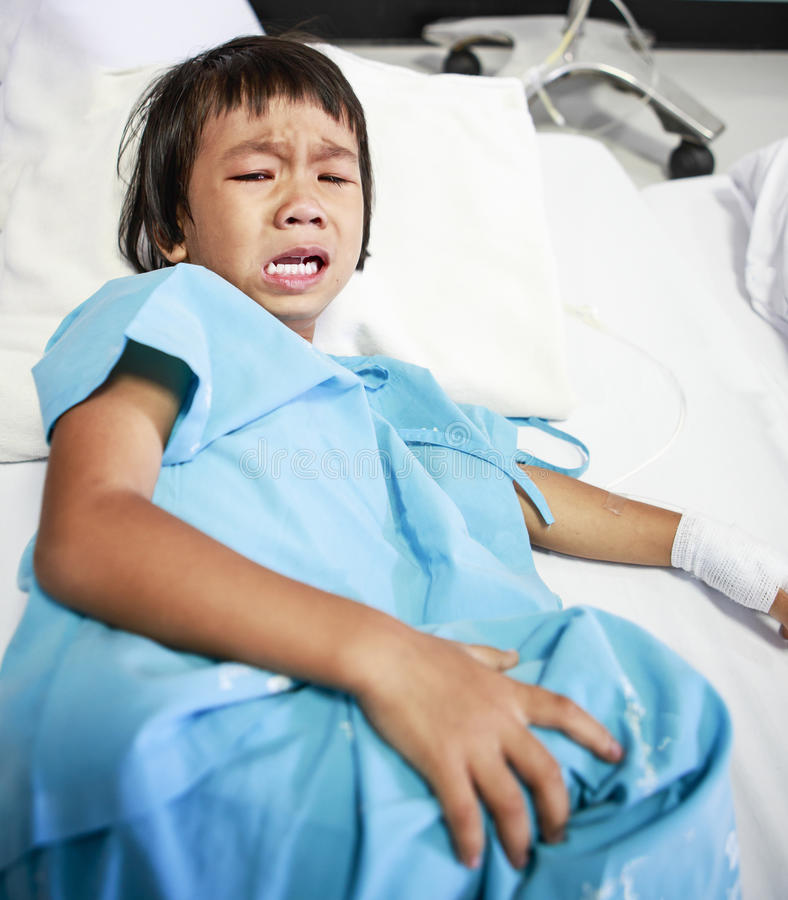 哭泣在医院病床上的病的小女孩 免版税库存图片