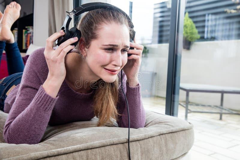 哭泣在去除的少妇她的喧闹的音乐的耳机 图库摄影