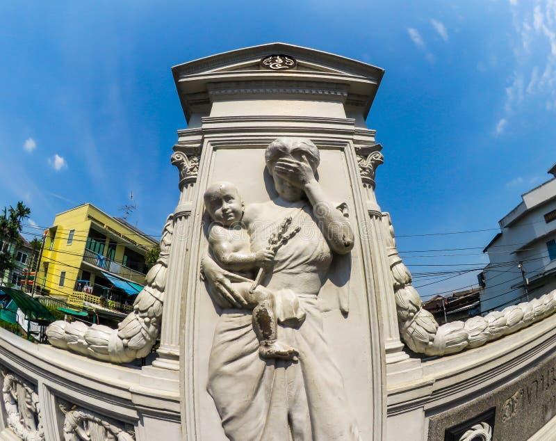 哭泣妇女偶象白色浅浮雕的雕塑和运载她自己的儿子在Mahadthai Autid桥梁 免版税库存照片