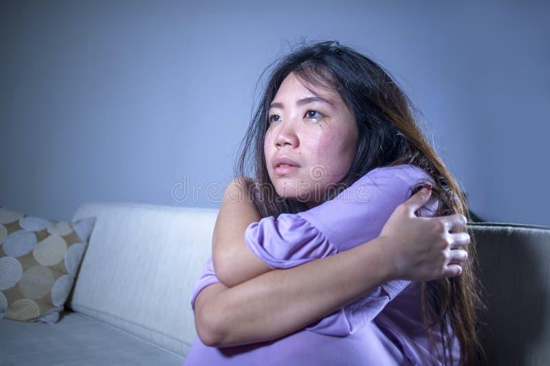 哭泣年轻哀伤和沮丧的亚洲中国妇女在家沙发的长沙发绝望和无能为力的遭受的忧虑和消沉感受 库存照片
