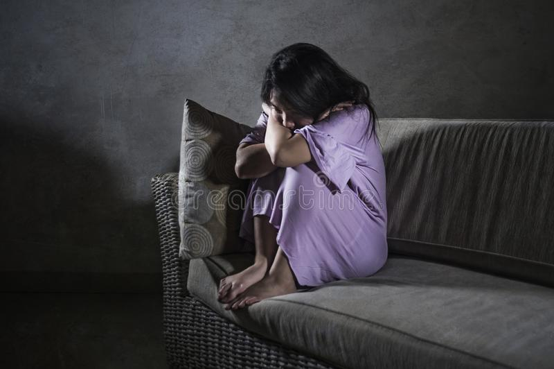 哭泣年轻哀伤和沮丧的亚洲韩国妇女在家沙发的长沙发绝望和无能为力的遭受的忧虑和消沉feeli 免版税库存图片