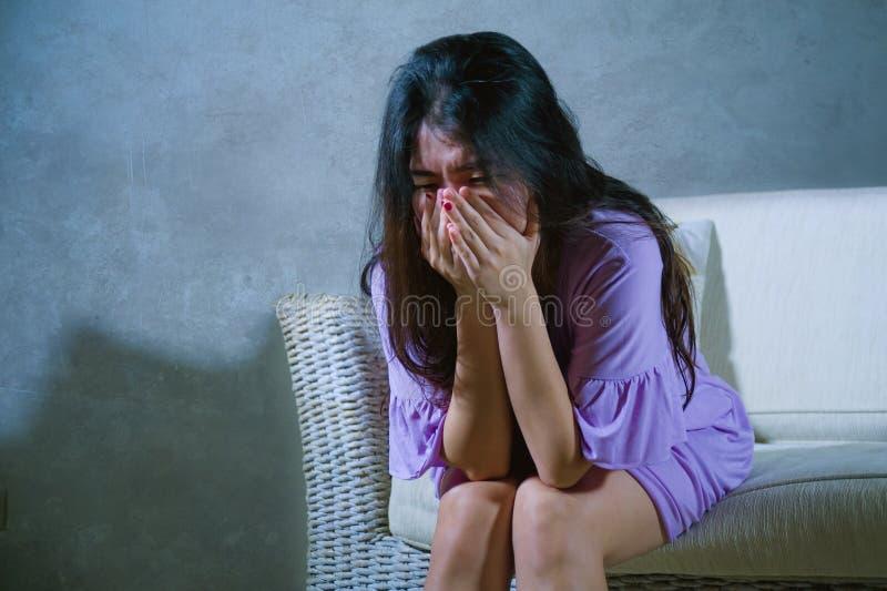 哭泣年轻哀伤和沮丧的亚洲韩国妇女在家沙发的长沙发绝望和无能为力的遭受的忧虑和消沉feeli 库存照片