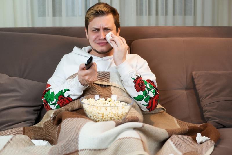 哭泣年轻的帅哥,当观看接触电影用在轻松的沙发时的玉米花 免版税图库摄影