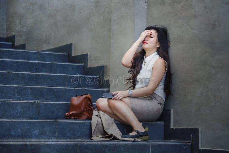 哭泣沮丧和绝望亚裔中国的女实业家单独坐街道楼梯痛苦重音和消沉 免版税库存图片