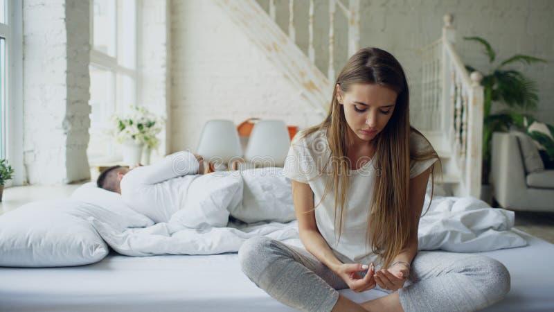 哭泣沮丧的少妇坐在床上和,当她的在家时在床上的boylfriend 免版税图库摄影