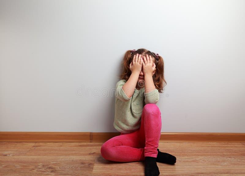 哭泣的不快乐的孩子女孩坐与闭合的面孔的地板 免版税库存照片