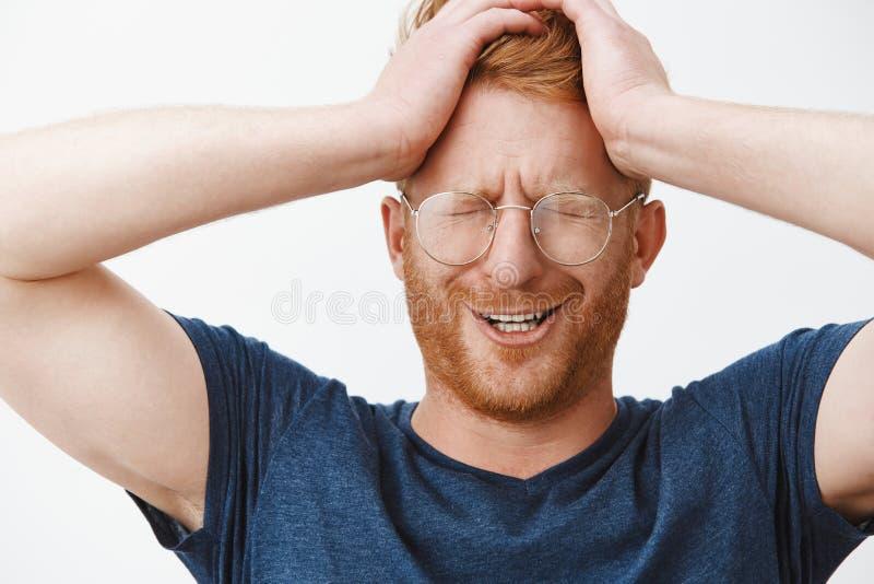 哭泣的人认为他为什么是一个谁在麻烦得到了 在握在头的玻璃的抱怨的生气的逗人喜爱的红头发人手 图库摄影