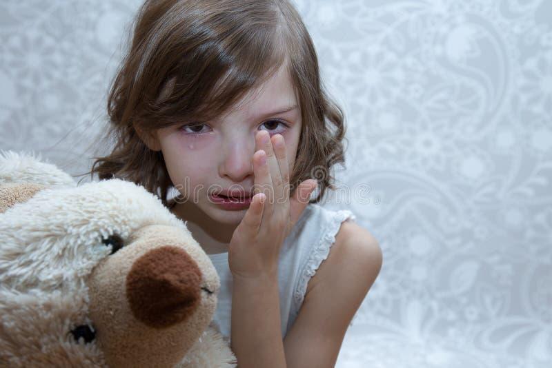 哭泣的女孩 她坐在桌上 库存照片