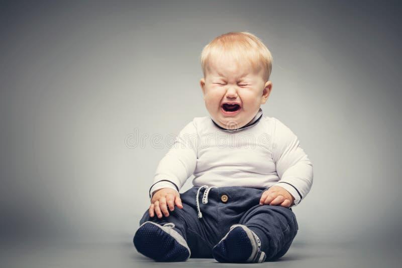 哭泣的婴孩坐地面 库存图片