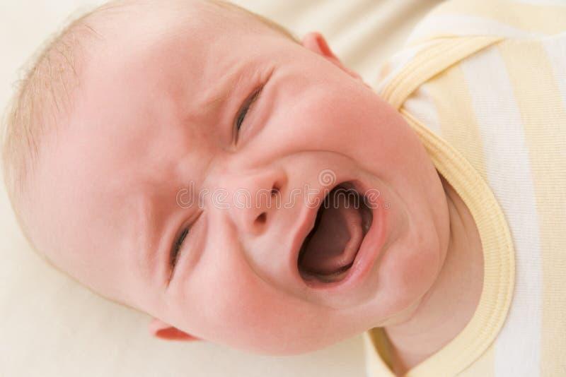 哭泣的婴孩户内位于 免版税库存照片