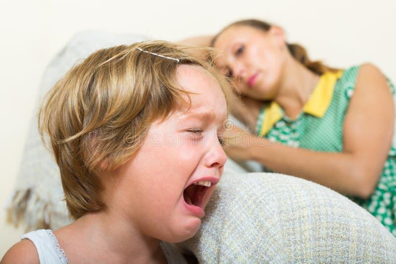 哭泣的孩子和母亲在家 免版税图库摄影