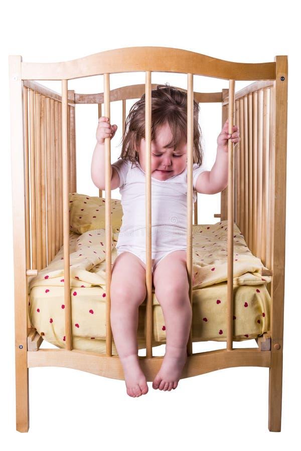 哭泣的小女孩,当坐在床上时 免版税图库摄影