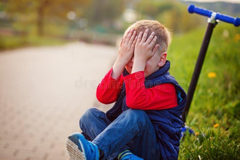 哭泣的小男孩,从在露天的滑行车跌倒了 免版税库存照片