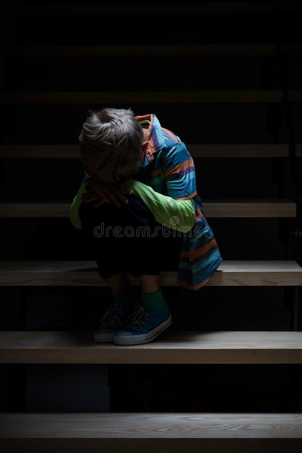 哭泣的男孩坐楼梯 免版税库存图片