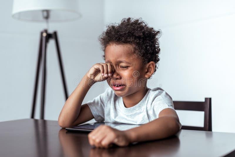 哭泣的男孩,当坐与片剂时 免版税库存照片