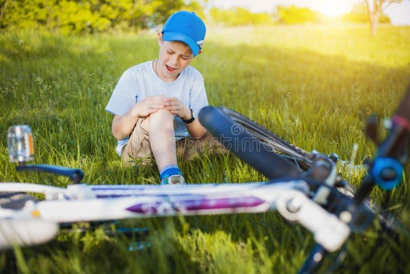 哭泣的男孩以在自行车附近的出血伤害 免版税库存图片