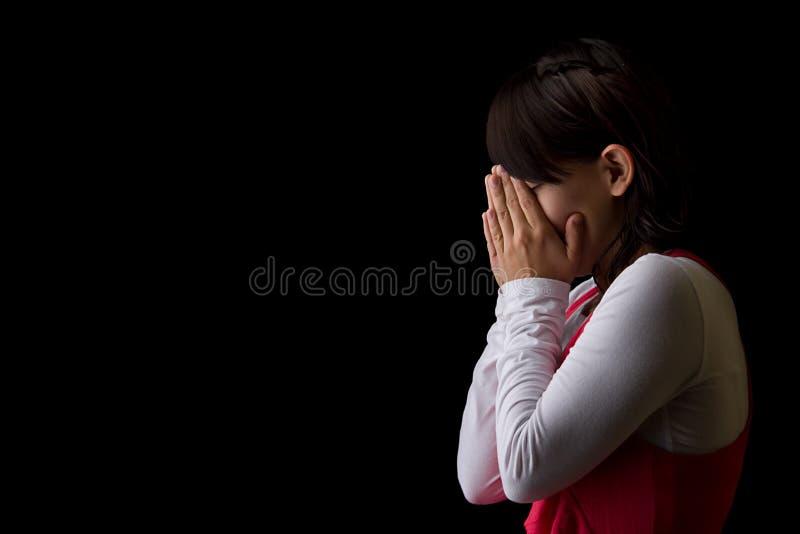 哭泣的讲西班牙语的美国人祈祷的妇女 免版税库存照片