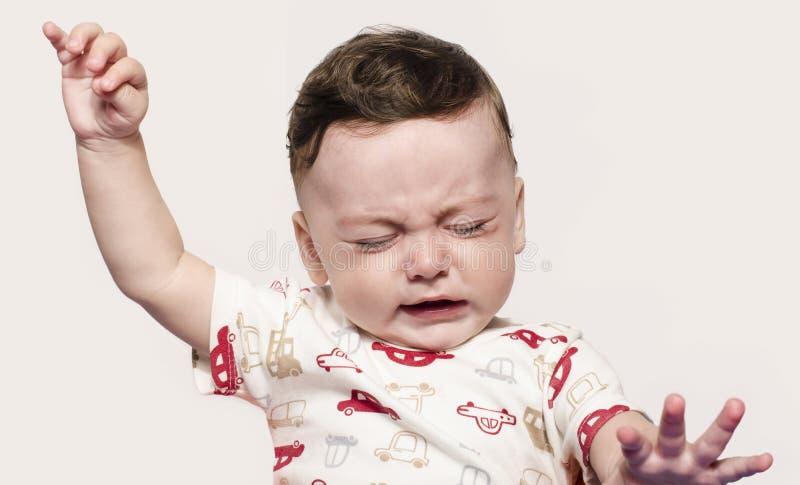 哭泣逗人喜爱的男婴举他的手  小孩在痛苦,痛苦,出牙中,拒绝和哭泣 免版税图库摄影