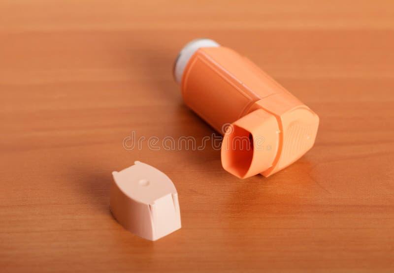 哮喘受害者的便携式的吸入器,木表面背景的  库存图片