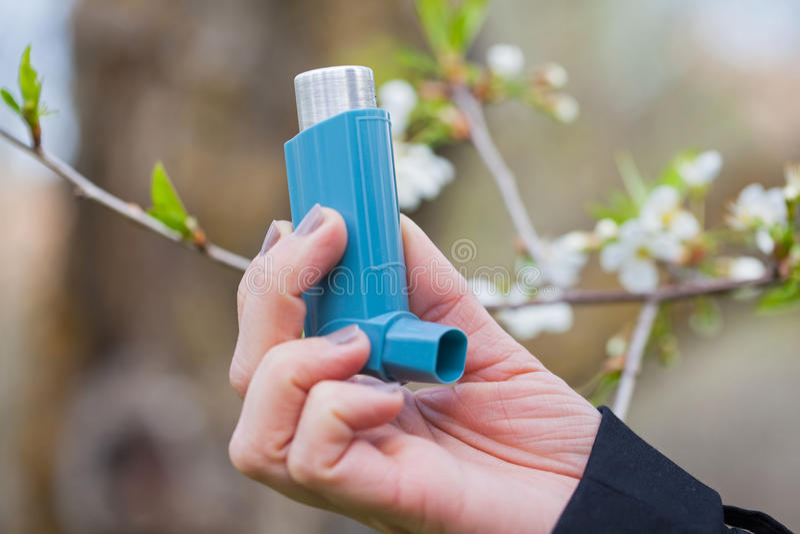 哮喘室外的吸入器关闭在春天期间 免版税库存图片