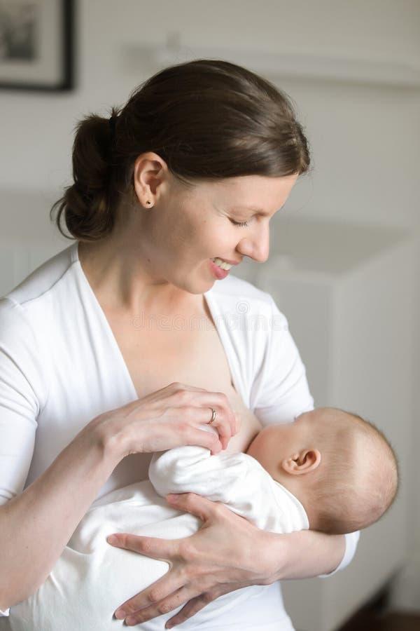 哺乳一个孩子,在她的手上的妇女的画象 库存图片