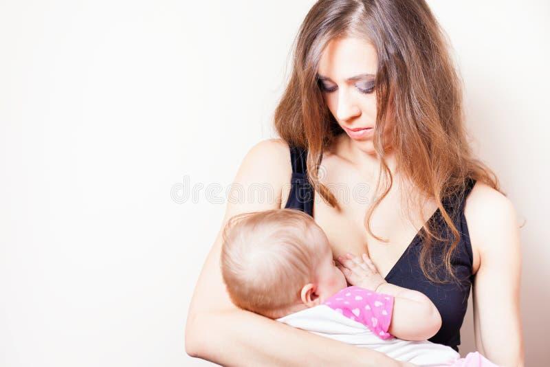 哺乳一个新出生的婴孩的美丽的母亲 免版税库存照片