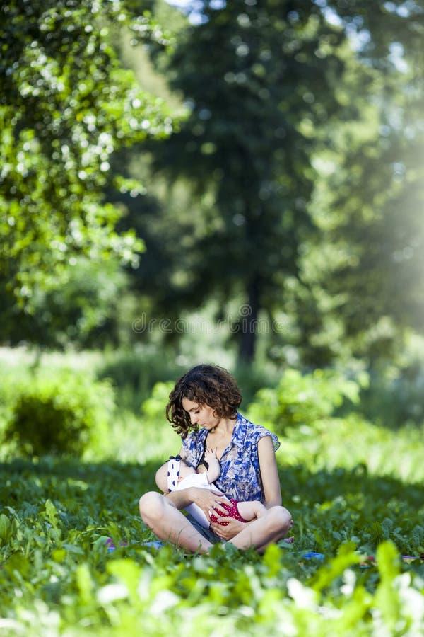 哺乳一个婴孩的年轻母亲在公园 免版税库存照片