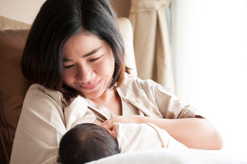 哺乳她在窗口旁边的母亲新出生的婴孩 从母亲` s乳房的牛奶是自然医学给婴孩 结合c的母亲节 免版税库存照片