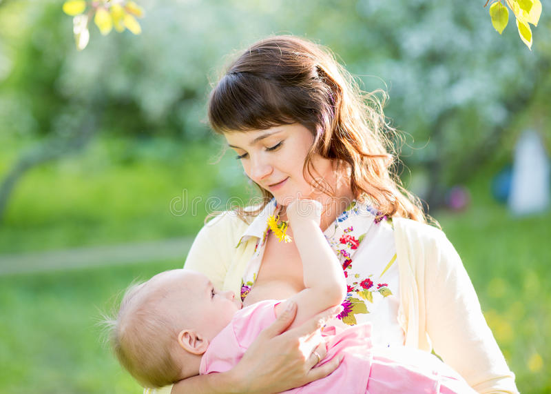 哺乳她的女婴的年轻母亲户外 免版税库存照片