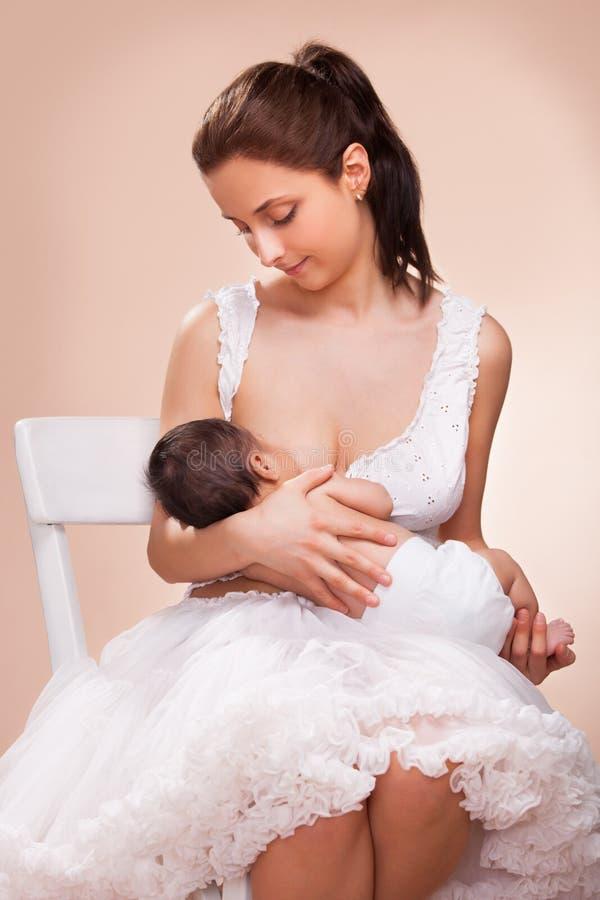 哺乳她的孩子的母亲 免版税库存图片