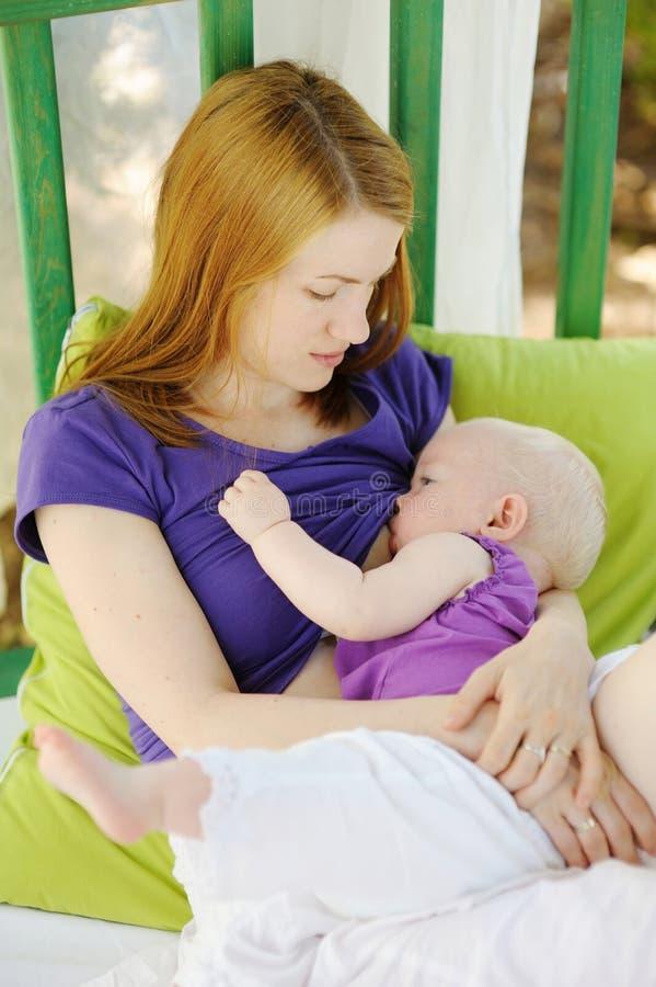 哺乳她的母亲的婴孩 免版税图库摄影