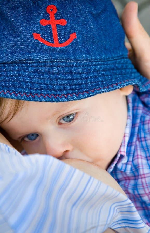 哺乳她的母亲的男婴 库存照片