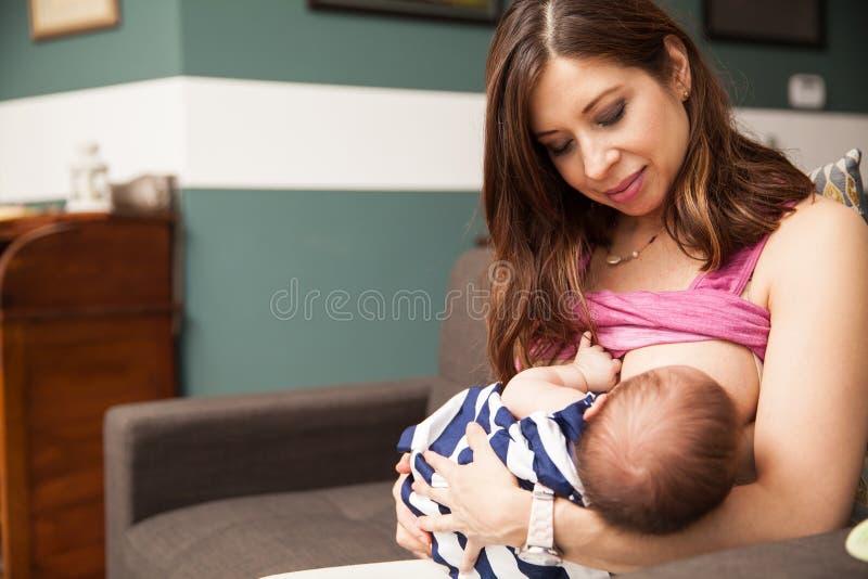 哺乳她的婴孩的俏丽的妈妈 库存照片